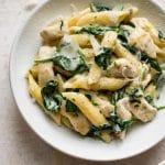 chicken spinach pasta in a white bowl
