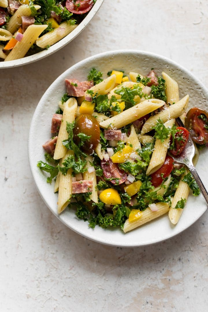 kale pasta salad in two small white bowls