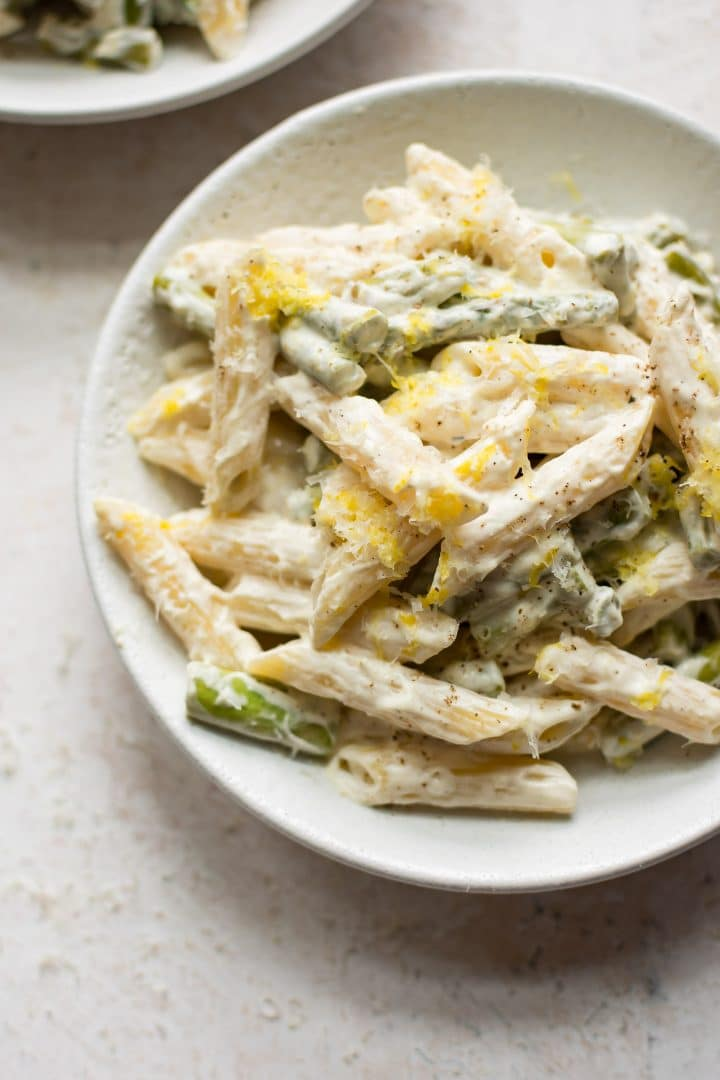 creamy asparagus pasta in white bowl