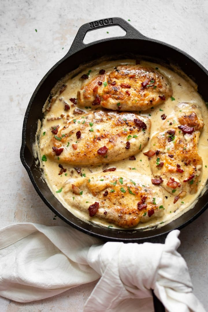 chicken breasts in creamy bacon sauce in a skillet