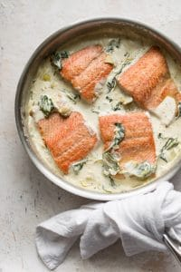 spinach and artichoke salmon in a skillet