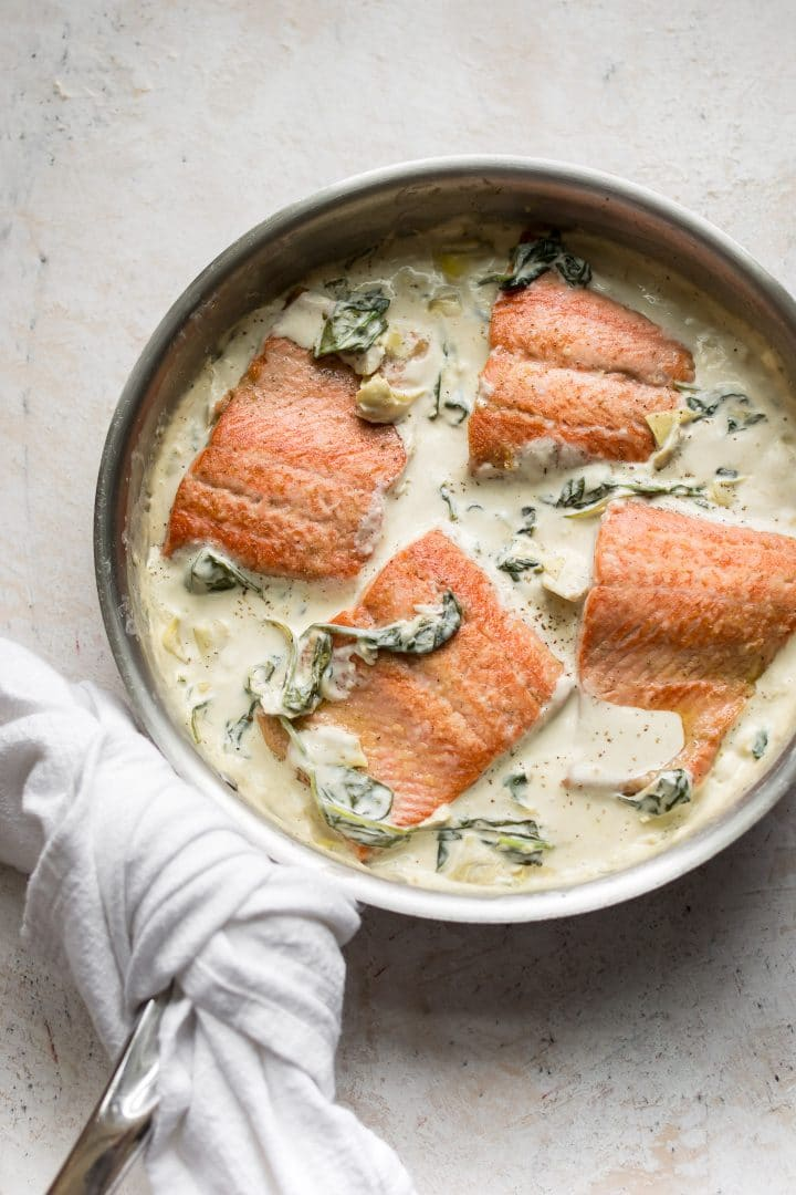 salmon in a creamy spinach and artichoke sauce in a skillet