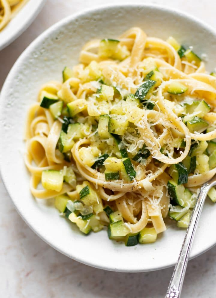 zucchini pasta in a white bowl with fettuccine and a fork