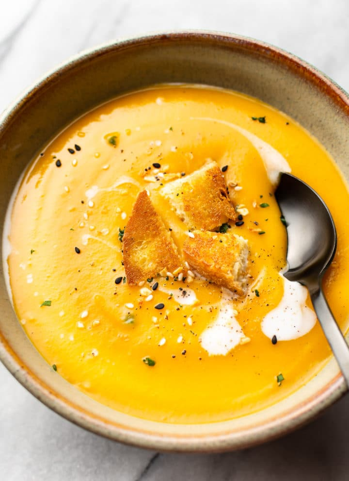 the best butternut squash soup with coconut milk (in a bowl with a spoon, on a marble background, topped with croutons)
