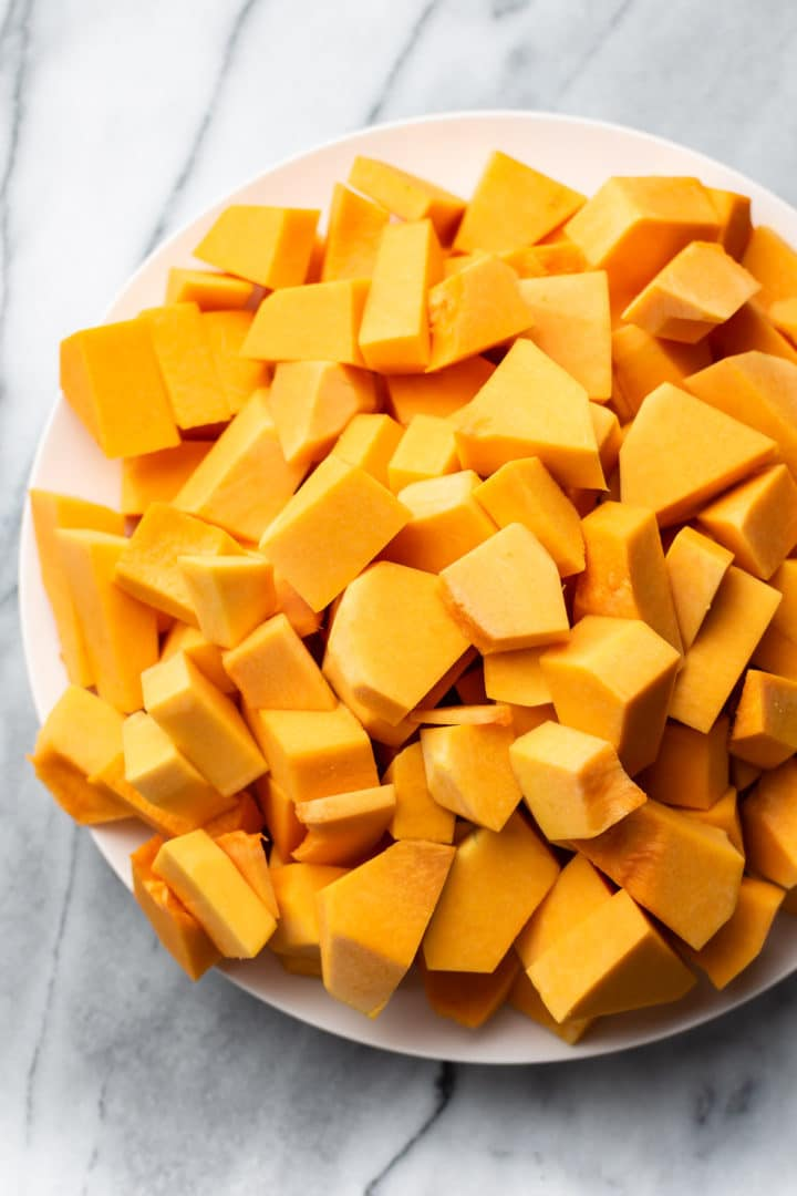 chopped raw butternut squash on a white plate and marble background