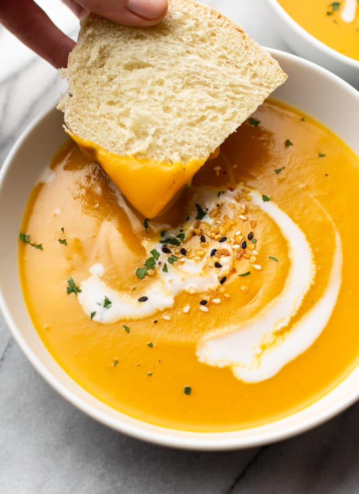 close-up of bread being dipped in a bowl of Instant Pot butternut squash soup