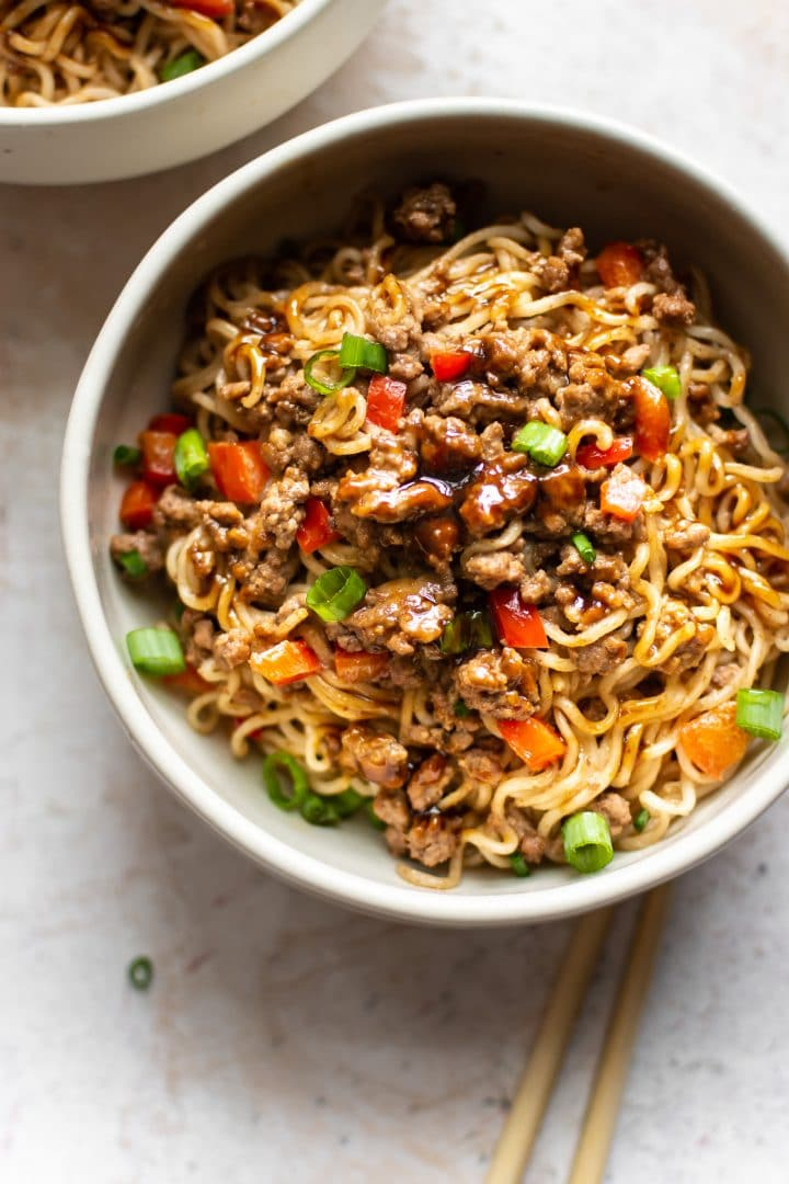 Asian beef noodles in a bowl with chopsticks, scallions, red peppers, and extra hoisin sauce