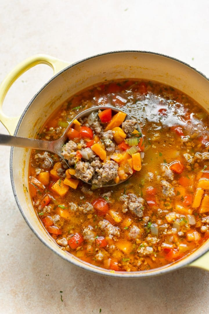 sausage and sweet potato soup in a yellow pot with a ladle of soup