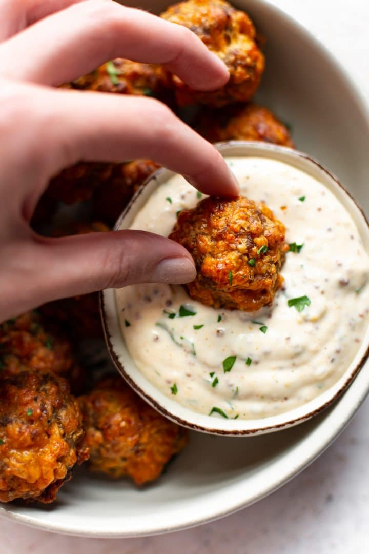 close-up of sausage ball being dipped in remoulade sauce