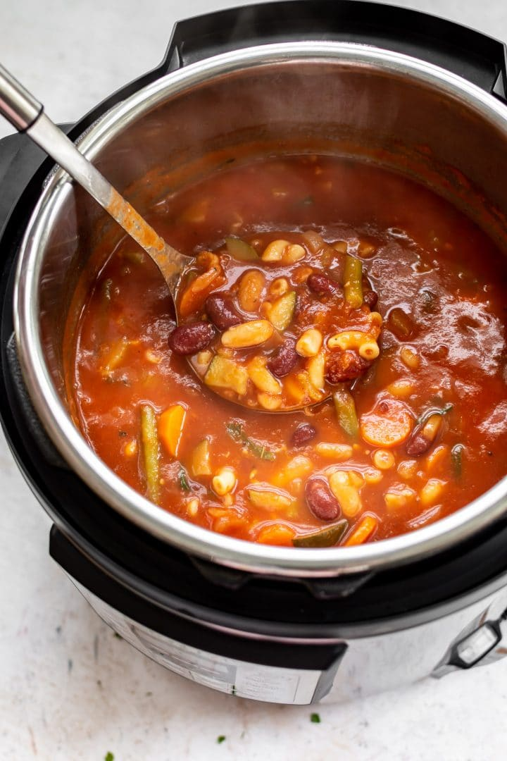 The best Instant Pot minestrone soup (pictured in the electric pressure cooker with a ladle)