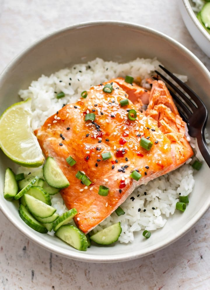 sweet chili glazed salmon in a bowl with rice, scallions, cucumber, lime, and sesame seeds