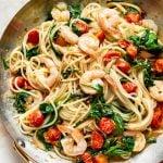 tomato spinach shrimp pasta in a skillet