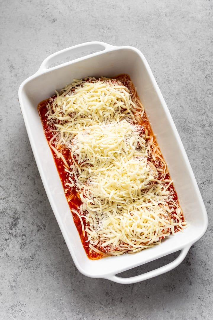 chicken breasts topped with parmesan and mozzarella - ready for the oven!