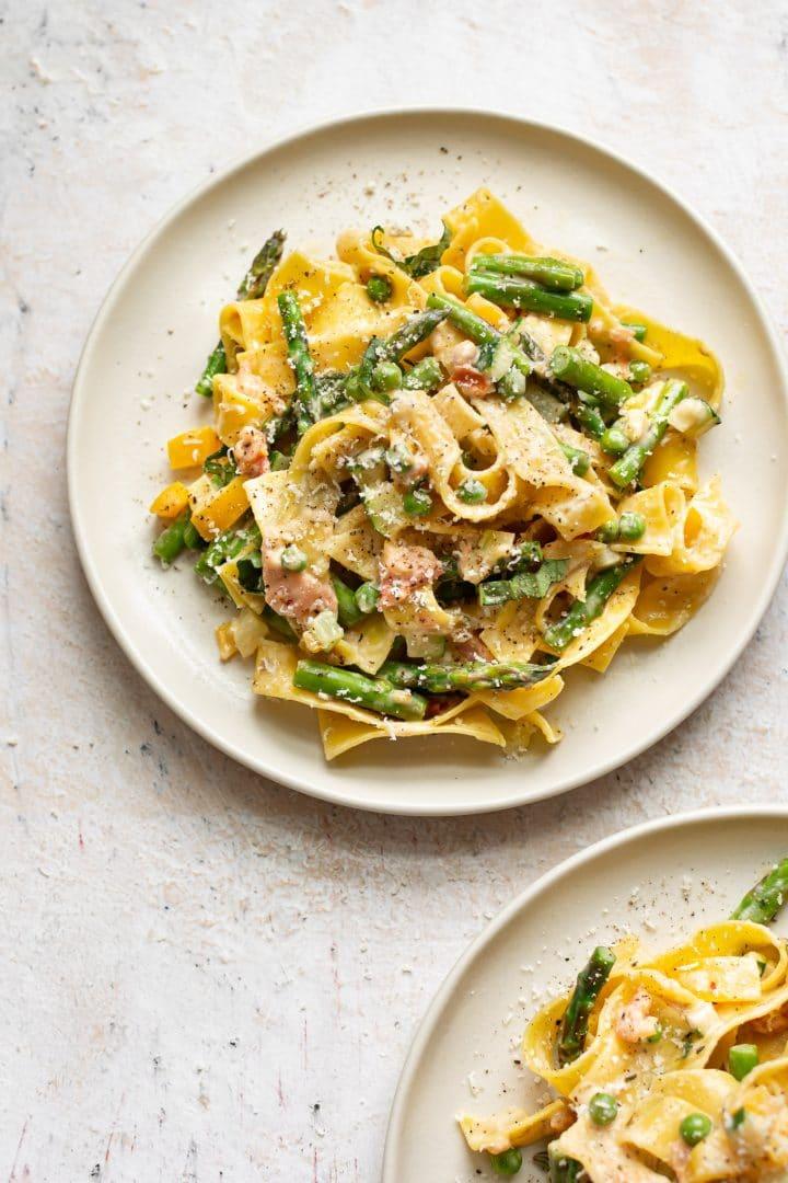 two plates of creamy pasta primavera