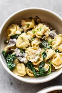 close-up of spinach tortellini with mushrooms in a white bowl