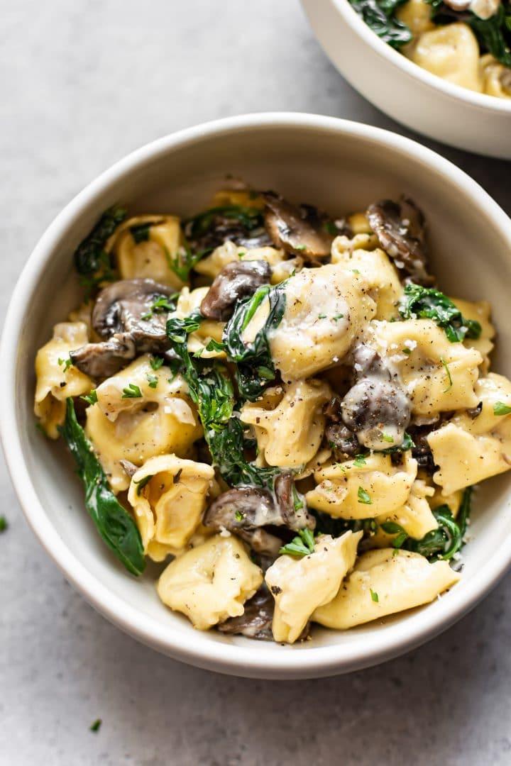 creamy spinach mushroom tortellini in two bowls