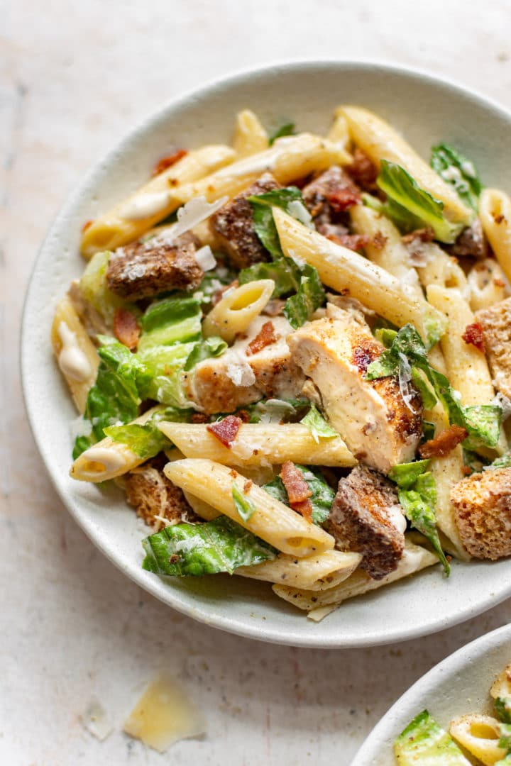 chicken caesar pasta salad plated in two bowls