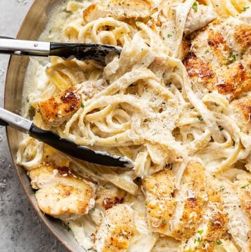 close-up of chicken fettuccine alfredo in a skillet being tossed with cooking tongs