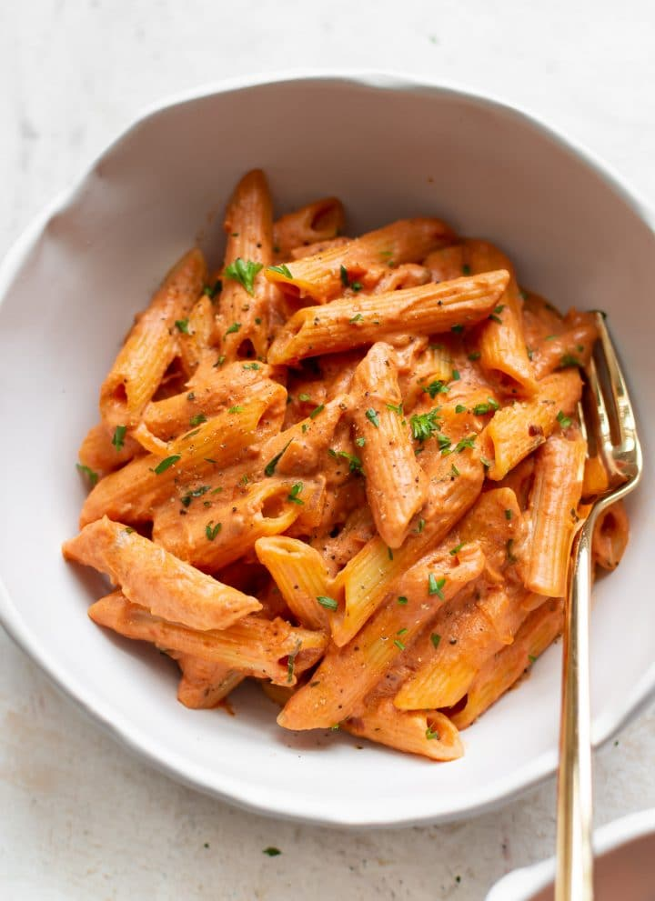 tomato and goat cheese penne close-up with a gold fork
