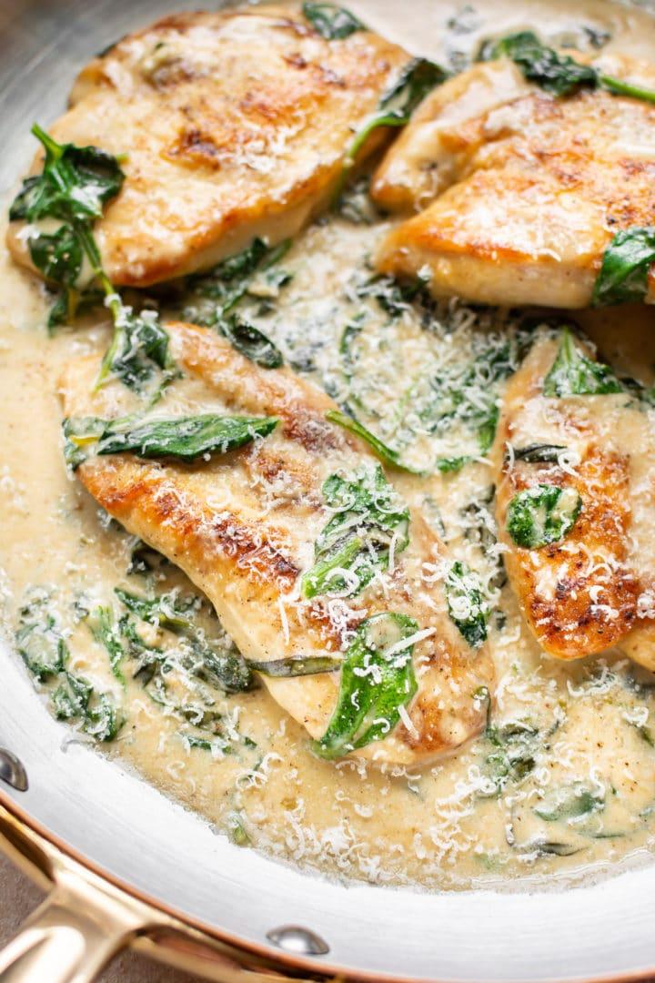 chicken florentine (chicken in spinach garlic cream sauce) close-up in skillet