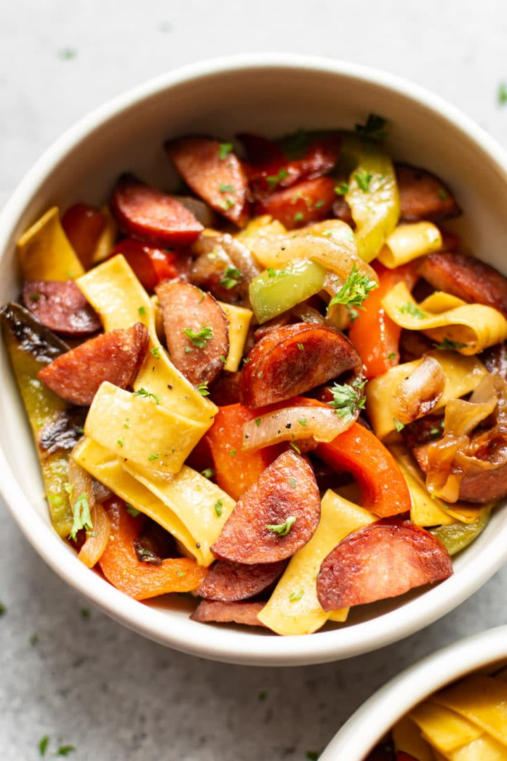 bowl of sausage peppers and onions served with egg noodles