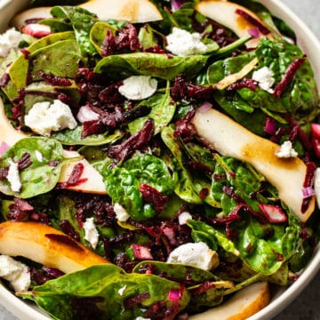 beet and spinach salad with pears, goat cheese, and a balsamic vinaigrette in a beige salad bowl