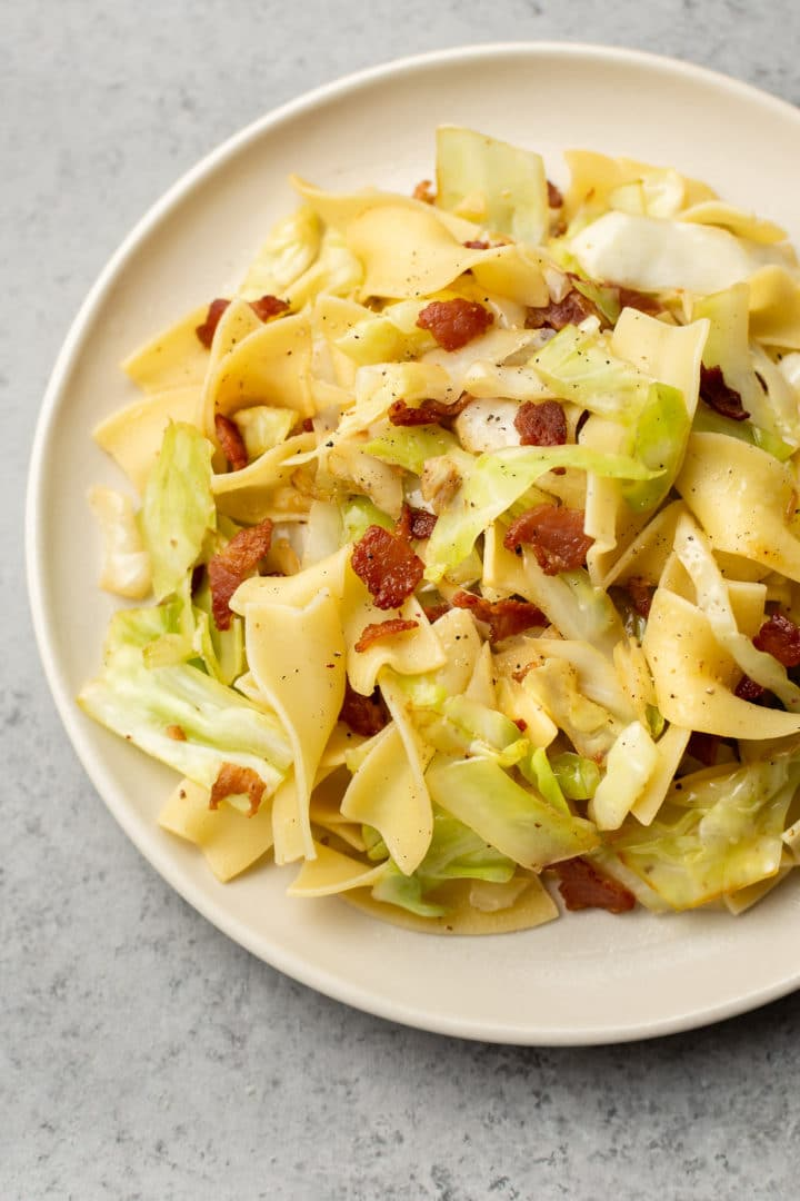close-up of cabbage and noodles with bacon (on a beige plate)