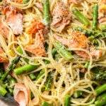 close-up in a copper skillet of creamy salmon and asparagus pasta