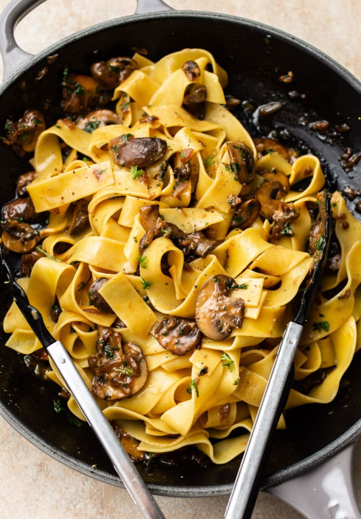 garlic butter mushroom pasta in a skillet with tongs to serve