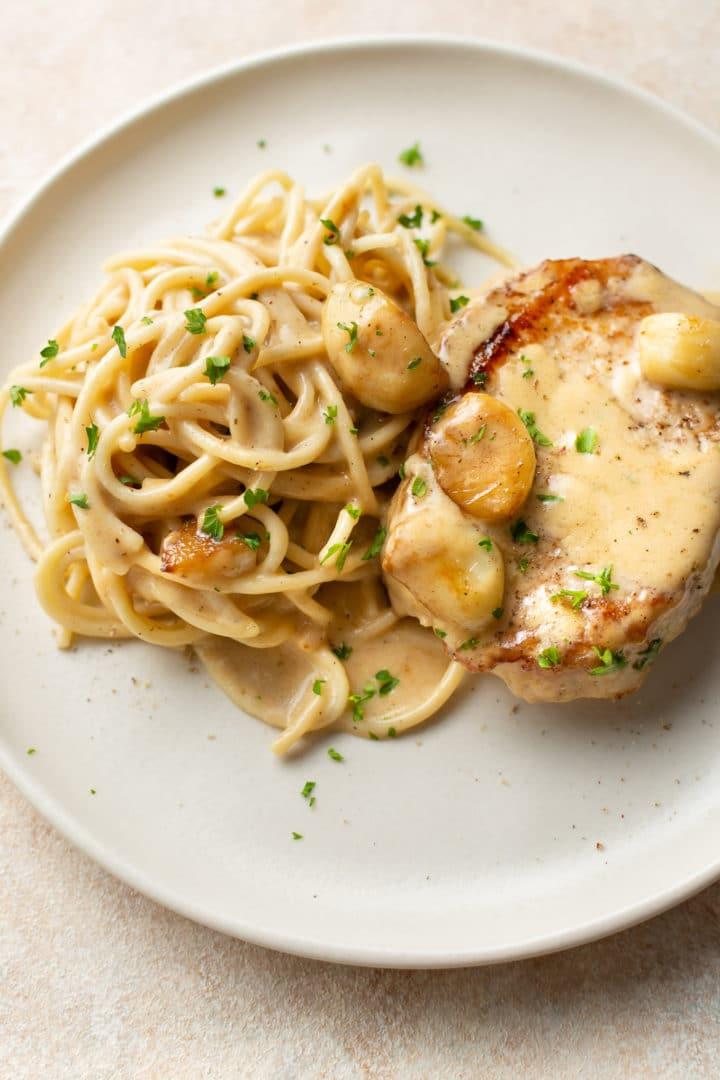creamy garlic pork chops plated with spaghetti