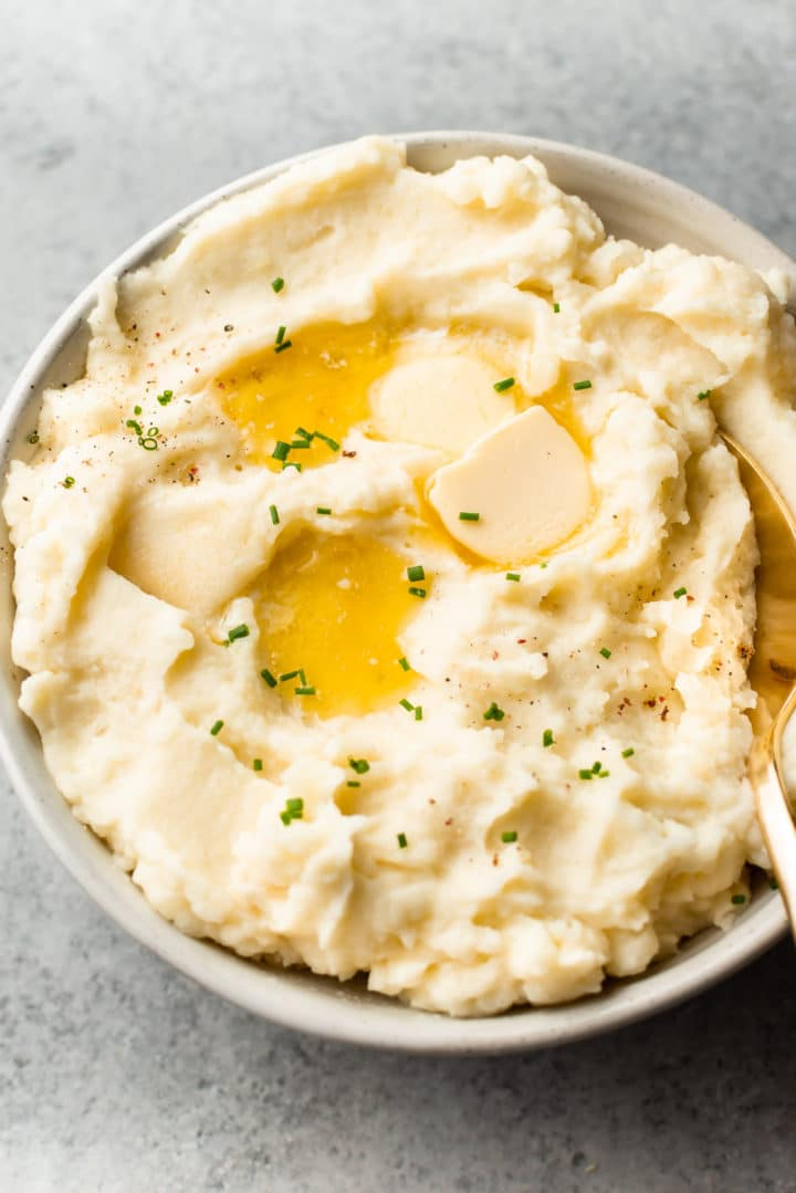the best garlic mashed potatoes in a beige bowl with plenty of butter on top!