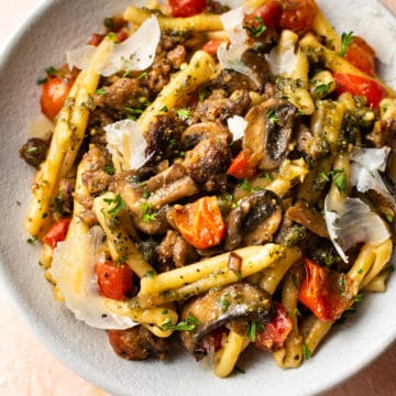 pesto sausage pasta in white bowl