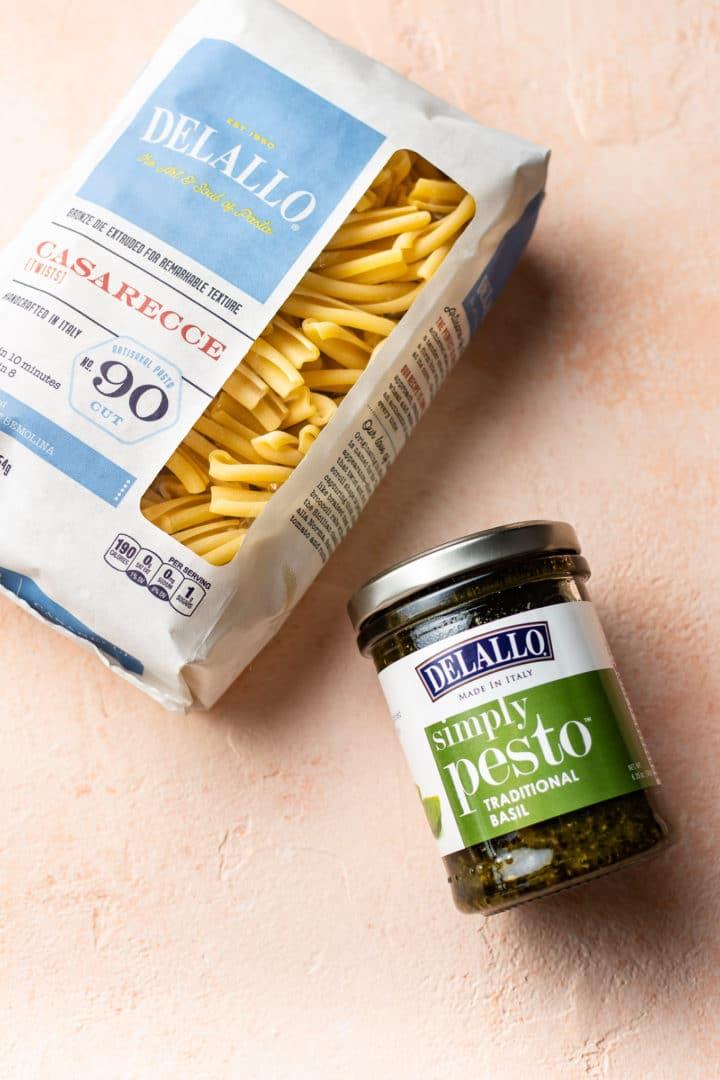 Delallo's Simply Peso and Casarecce Pasta on a peach-colored background