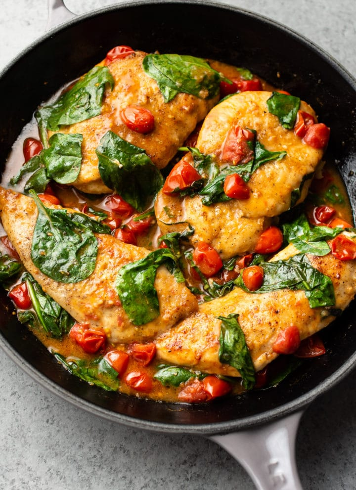 chicken breasts with a white wine, fresh tomato, and spinach sauce in a Le Creuset skillet