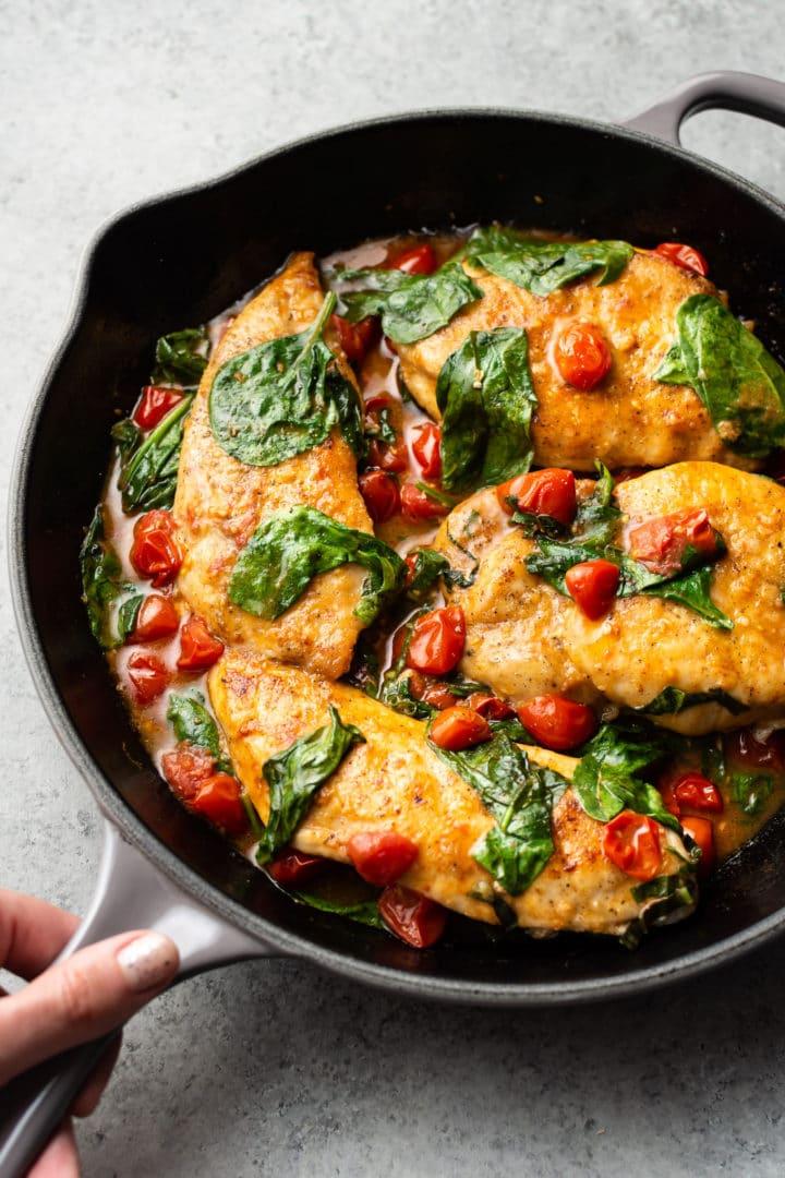 tomato spinach white wine chicken in a skillet