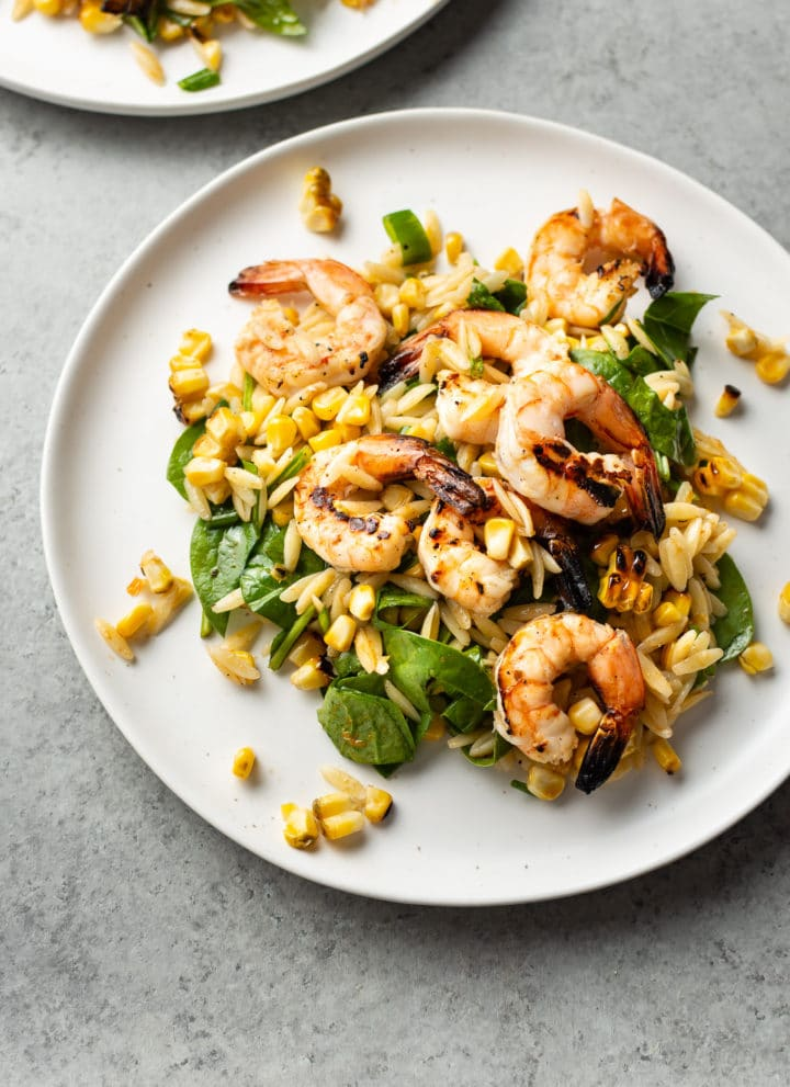 Cajun grilled shrimp and orzo salad on two white plates