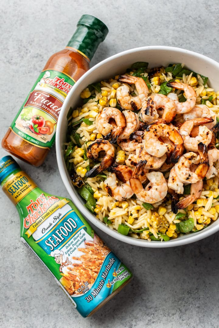 Cajun grilled shrimp orzo salad surrounded by Tony Chachere's Seafood Marinade and Tony's Chachere's French Dressing
