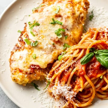 chicken parmesan on a plate with spaghetti tossed with marinara sauce and fresh basil and parmesan grated on top