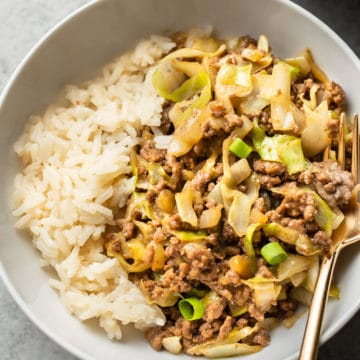 close-up of beef and cabbage stir fry with rice in a white bowl