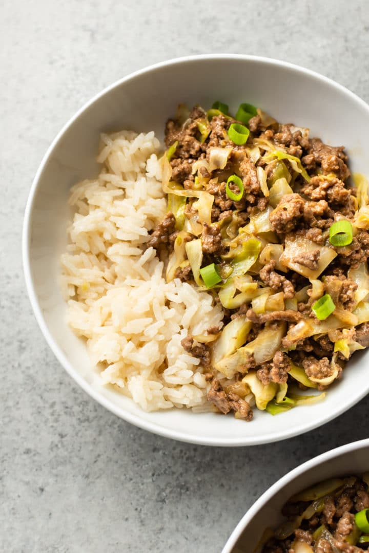 ground beef and cabbage stir fry with rice in two white bowls