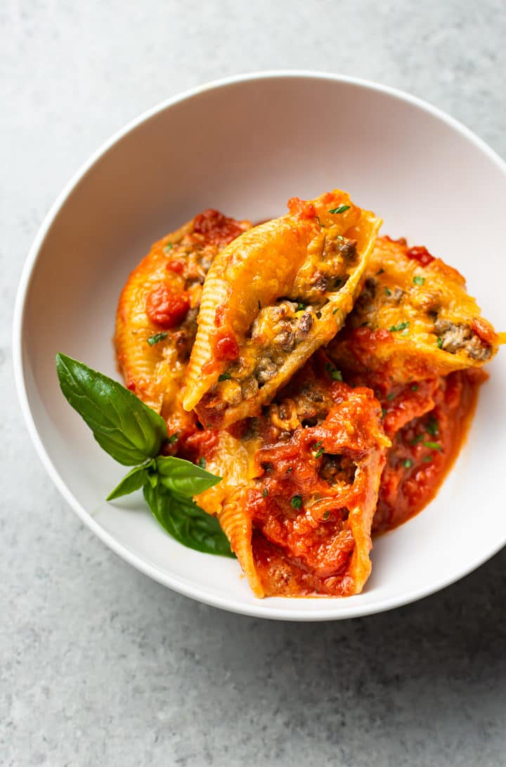 beef stuffed shells in a white bowl with a sprig of fresh basil