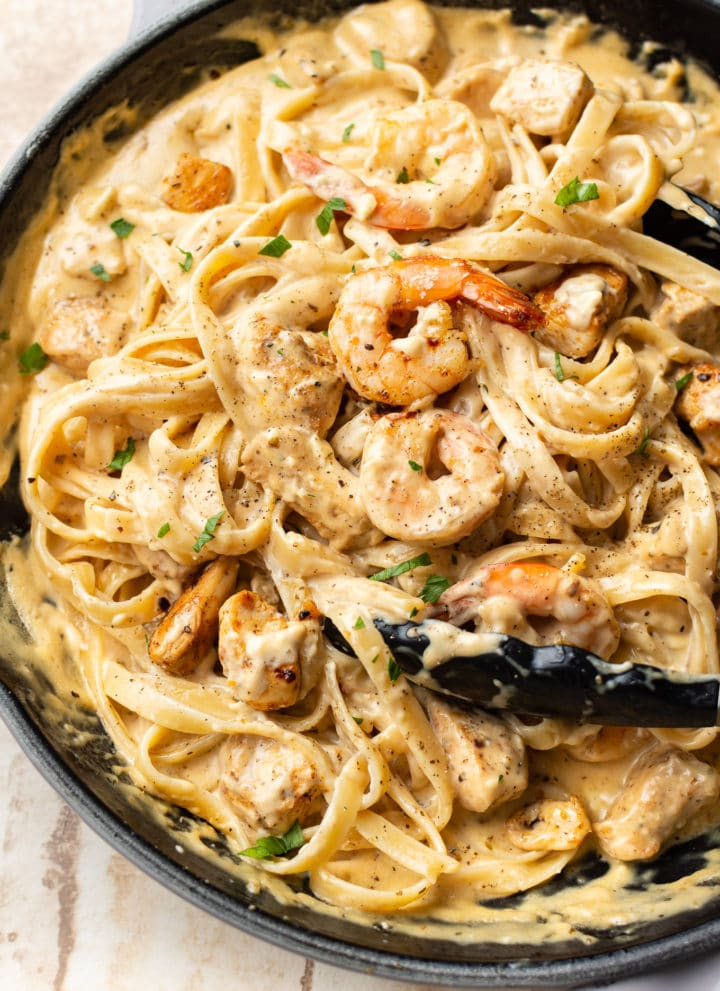 Cajun chicken and shrimp Alfredo in a skillet (being tossed with cooking tongs)