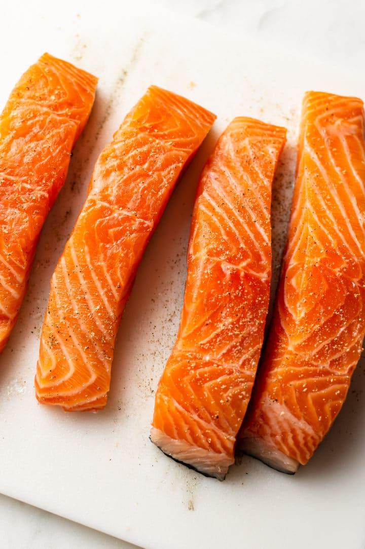 4 fresh salmon pieces on a cutting board