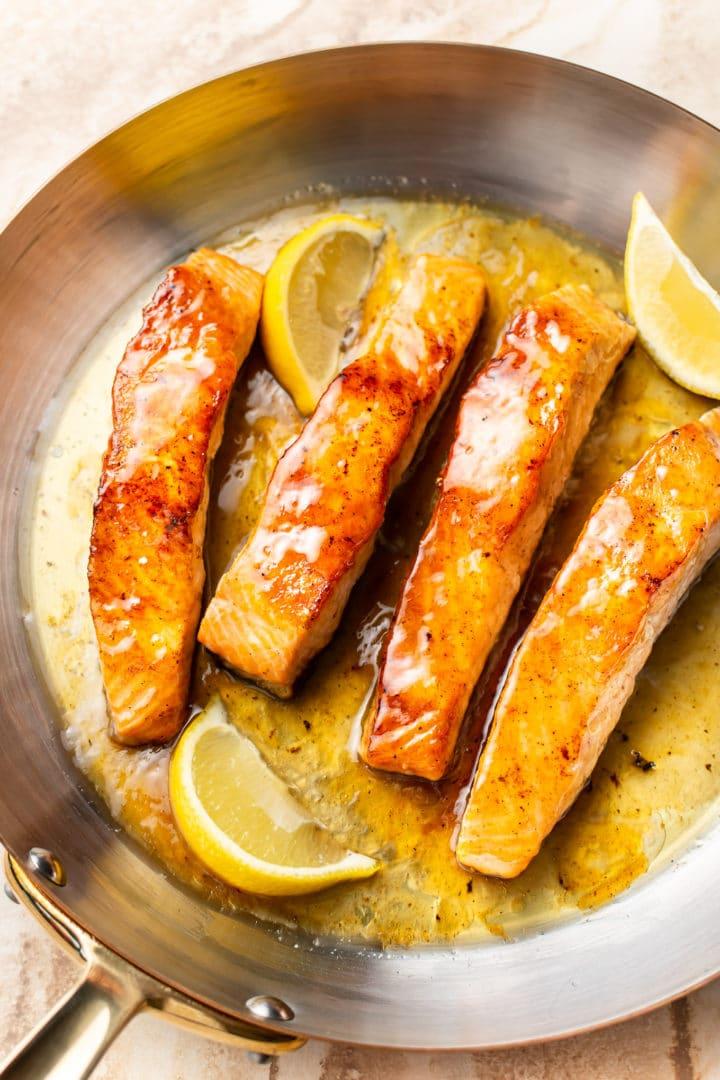 honey lemon butter salmon in a skillet with fresh lemon wedges