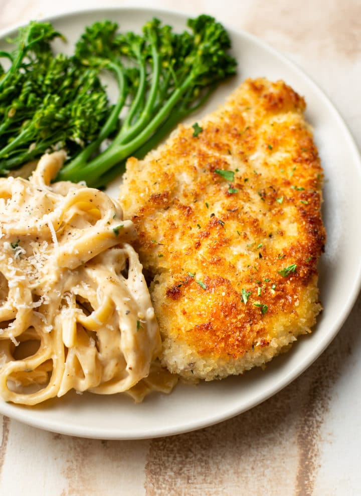 crispy parmesan crusted chicken on a plate with Fettuccine Alfredo and broccolini