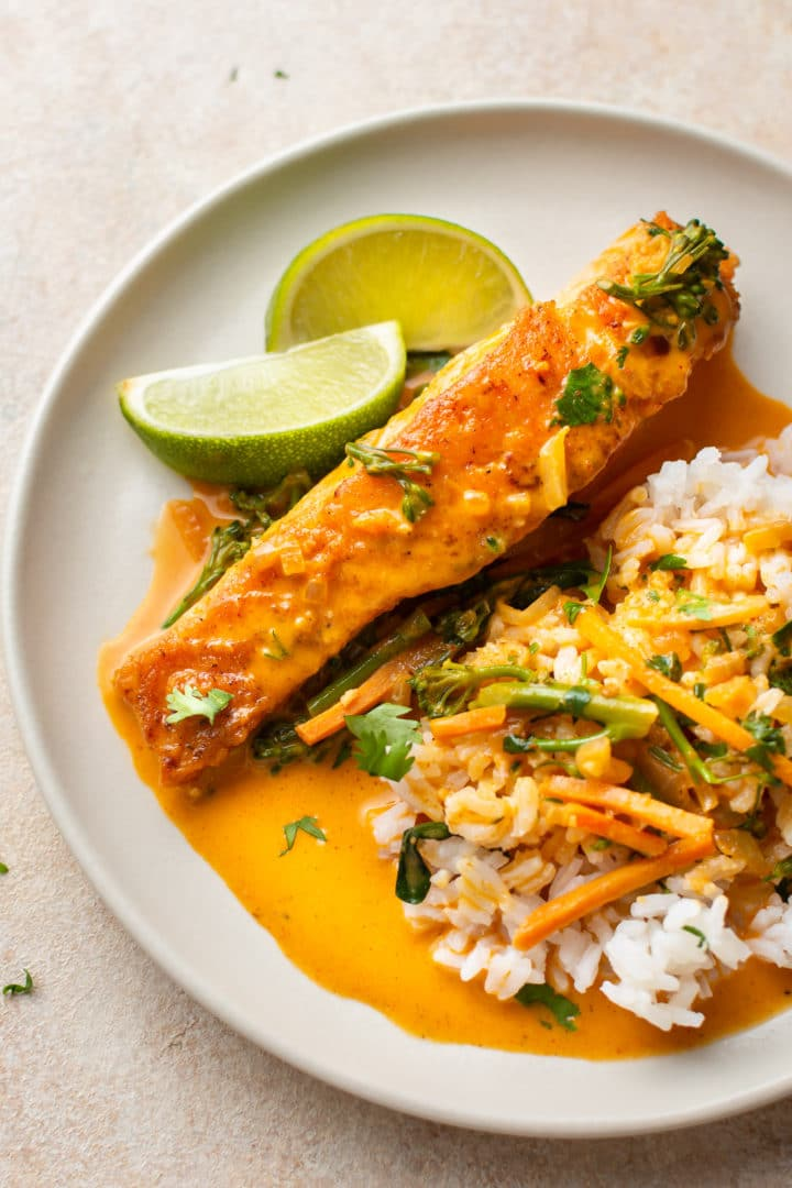 Thai coconut curry salmon on a plate with rice, tons of sauce, and lime wedges