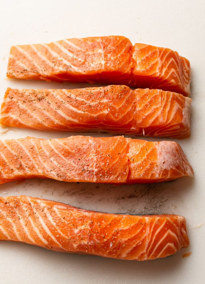 uncooked salmon on a board cut into 4 equal pieces