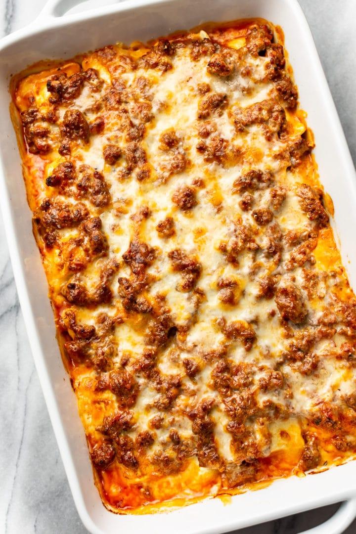 cheesy ravioli bake in a white baking dish