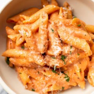 creamy tomato pasta in a white bowl