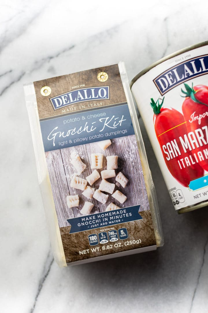 DeLallo's gnocchi kit & a 28 ounce can of DeLallo's San Marzano style crushed tomatoes on a marble background